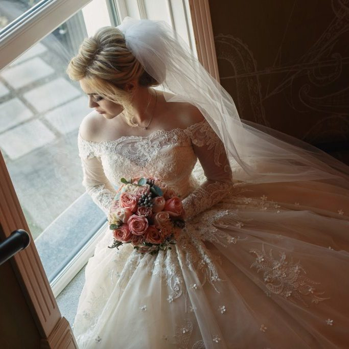 portrait-cute-bride-with-bridal-bouquet-pink-roses-indoor-pretty-happy-bride-luxury-dress-long-veil-near-window-young-bride-with-beautiful-neckline-holding-bouquet-flowers